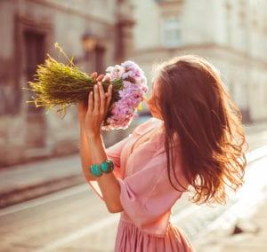 Photo ambiance bois de rose, joie, fleur, mode, look, douceur. Photo représentant une femme dans la rue avec un bouquet de fleur.